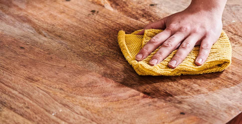 wiping acacia table with cloth